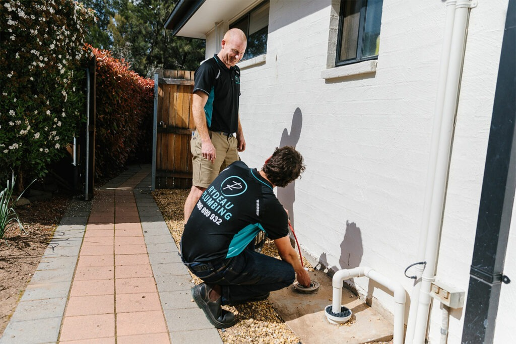 two persons fixing blocked drains